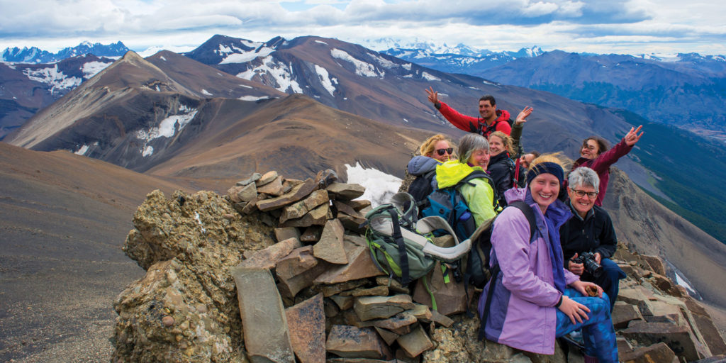 People smiling on top of the mountain in Patagonia. This is one of the best treks in South America