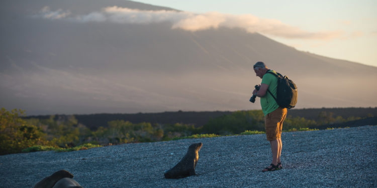 Contours Travel- Man with a seal by the beach in Galapagos